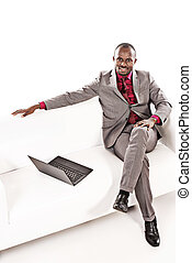 Confident african american business man working on his laptop on a sofa. Isolated over white.