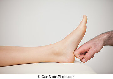 Forefinger touching a barefoot in a room