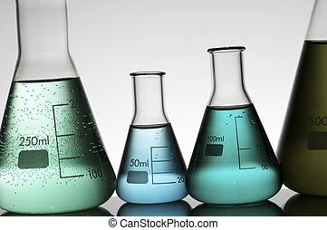laboratory - forefront of a laboratory flasks containing...