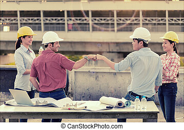 Foreign investor and Engineer Fist Bump for celebrate after construction project was successful and Their Secretary stood behind