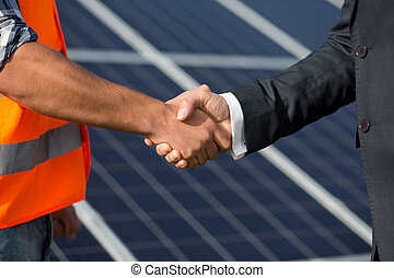 Foreman and businessman shaking hands at solar energy station.
