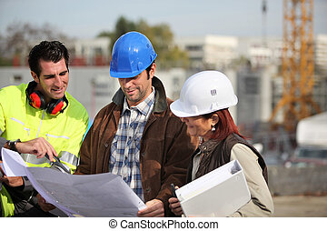 Foreman and two colleagues examining plans
