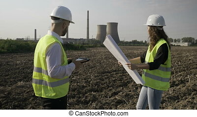 Foreman and young female engineer discussing project details using tablet pc and blueprint outdoor near petrochemical factory