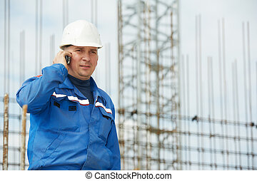 foreman at construction site with mobile phone
