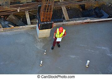 Foreman builder inspecting concrete construction