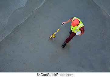 Foreman builder measuring concrete floor with a rolling tape measure