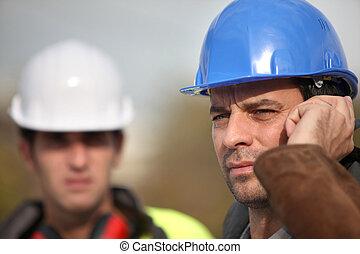 Foreman communicating via radio