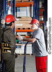 Foreman Communicating With Coworker At Warehouse