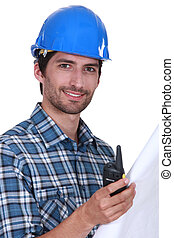 Foreman holding radio and plans