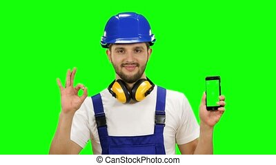 Foreman holds a phone in his hands and shows a thumbs up....