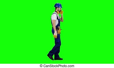 Foreman in a helmet and gloves speaks on the phone. Green screen. Side view