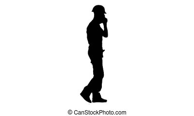 Foreman in a helmet and gloves speaks on the phone. White background. Silhouette. Side view