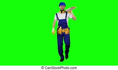 Foreman in a helmet goes to work with wooden boards in his hands. Green screen