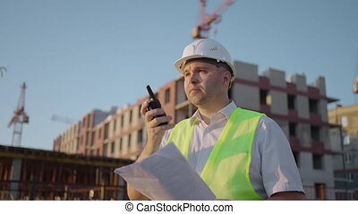 Foreman in helmet and vest talking on walkie-talkie with builders, standing at construction site, tracking shot. building expert engineers speaking using a radio with some builders , amazing sunlight.