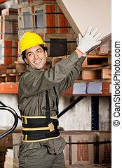 Happy foreman lifting a cardboard box at warehouse