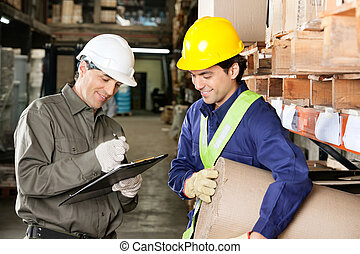 Foreman Looking At Supervisor Writing Notes