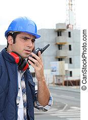Foreman on construction site giving orders via radio