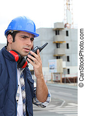 Foreman on construction site giving orders via radio