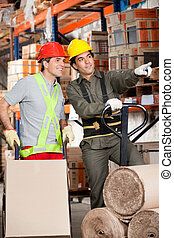 Foreman Showing Something To Coworker At Warehouse