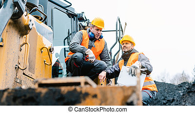 Foreman showing worker in open-cast mining pit direction