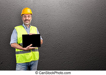 foreman smiling and showing a tablet