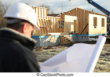 foreman turning his back to camera consulting blueprints in construction site