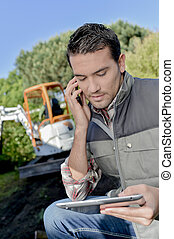 Foreman using a tablet and a mobile