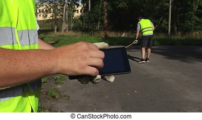 Foreman using tablet near worker who using brush