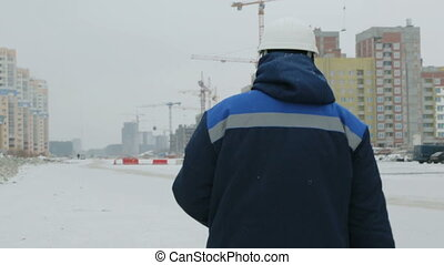 Foreman walking to the buildings under construction