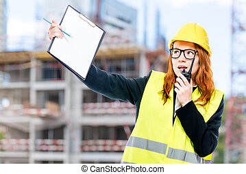 foreman with a walkie-talkie in a vest and a yellow helmet against the background of the building under construction