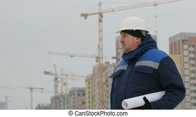 Foreman with brief case and drawings at construction project