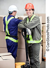 Foreman With Colleague Working At Warehouse - Portrait of...
