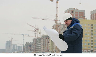 Foreman with paper drawing plan at construction project