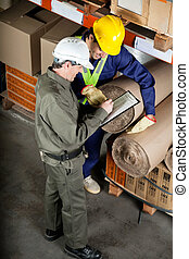 Foreman With Supervisor Writing Notes At Warehouse - High...