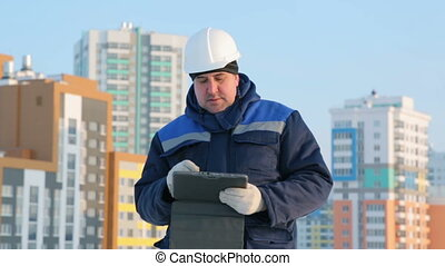 Foreman with tablet computer at major construction project