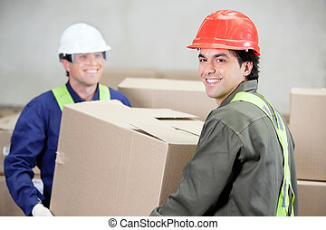 Foremen Lifting Cardboard Box At Warehouse - Two foremen...