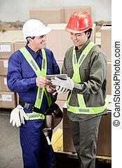 Foremen Using Digital Tablet in Warehouse