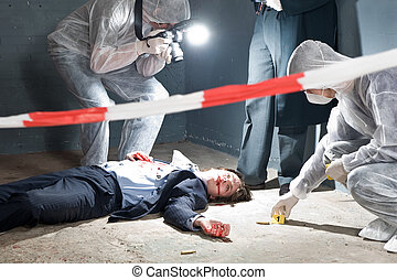 Murder scene with two forensic analysts and a police lieutenant investigating a crime on a businessman in a basement Murder scene with two forensic analysts and a police lieutenant investigating a crime on a businessman in a basement