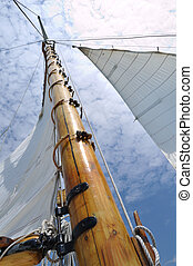 Foresail, Jib, and Wooden Mast of Schooner Sailboat on a Sunny Summer Day
