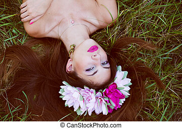 forest beauty fairy: image of beautiful brunette young woman with naked shoulders & flowers crown having fun relaxing looking at camera lying on green summer outdoors copy space background