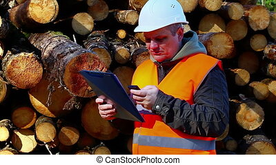 Forest employee with cell phone near stacks of logs