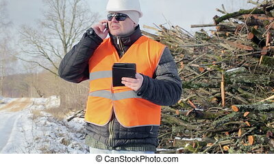 Forest engineer with tablet PC and cell phone near road