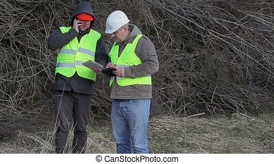Forest engineers talking near pile