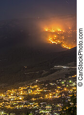 Forest fire burning at night nearly the city