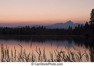 A fiery red sunset that is the result of smoke from the Lake George forest fire that burned in Central Oregon in the summer of 2006. The smoke particles in the air made the sky really red. The mountain on the horizon is Three-Fingered Jack in the Oregon Cascades.