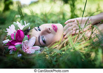 forest girl: closeup on beautiful young lady having fun lying relaxing on green grass outdoors copy space background