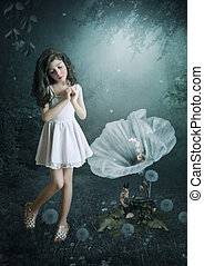 The little girl in magic forest spellbound listening to music from a gramophone, squirrel sits in the grass.