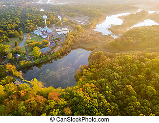 Forest in the autumn from a height a beautiful panorama of lake at sunrise, morning landscape