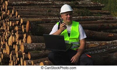 Forest inspector sitting and using walkie-talkie