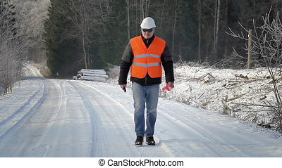 Forest inspector with walkie-talkie on the road in the woods